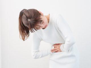 採卵後の腹痛と吐き気を感じる女性